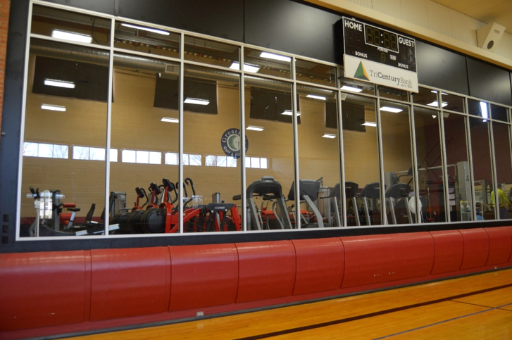 Row of exercise bikes behind a glass wall.