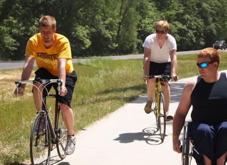 A wheelchair user and two bicyclists using a paved trail.