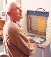 Man who is blind using an accessible voting machine.