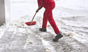 Person shoveling snow in front of building.